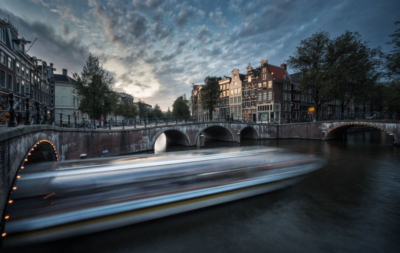 Canal cruise boat passing, Amsterdam canals Amsterdam Amsterdam Canal Canal Cruise Daytime Amsterdamcity Arch Architecture Blurred Motion Boat Bridge - Man Made Structure Building Exterior Built Structure City Clouds Color Connection Long Exposure Motion No People Outdoors Tourism Travel Destination Water