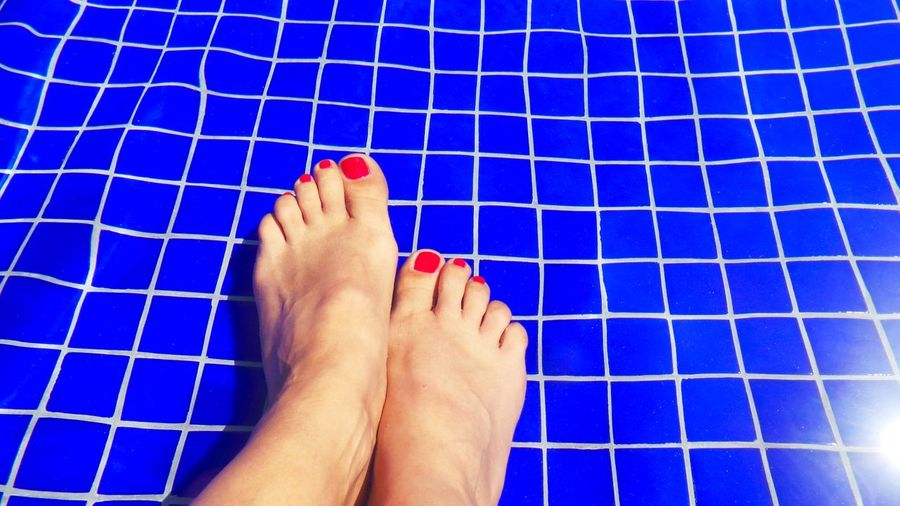 Low section of woman legs against swimming pool