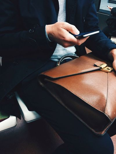 Midsection of businessman using smart phone while sitting with briefcase
