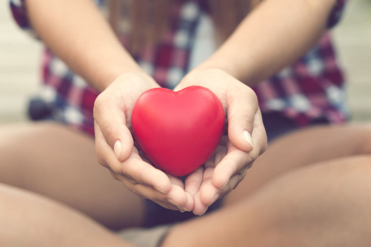 Woman holding a heart in the hands Hands Bonding Close-up Day Heart Heart Shape Holding Hope Human Body Part Human Hand Love Midsection Outdoors People Real People Red Romance Togetherness Two People Women