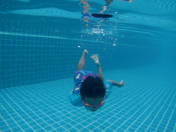 Rear view of boy swimming in pool