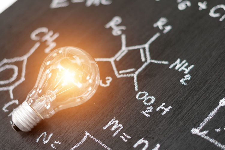 Digital composite image of illuminated light bulb over blackboard with formulas