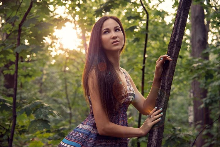 Thoughtful Young Woman Looking Away While Standing In Forest