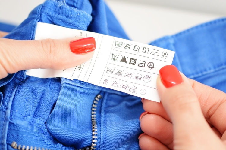 Cropped hands of woman holding jeans label with symbols