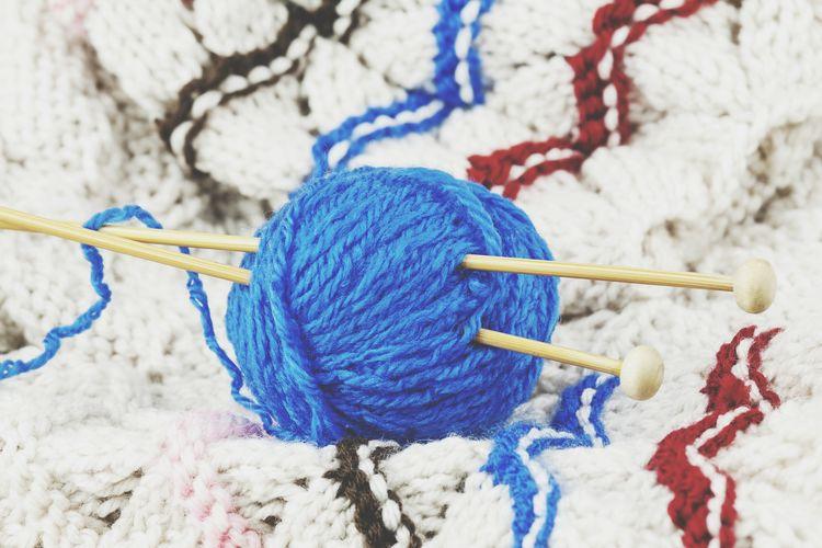 Blue wool thread ball on wool background