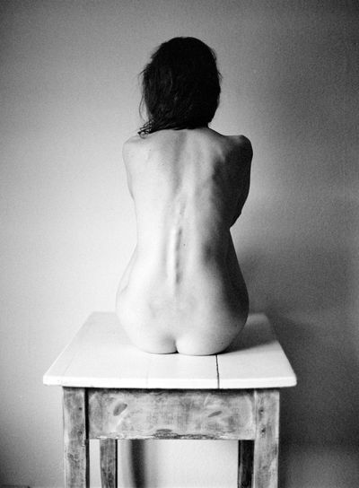 Rear view of shirtless woman sitting against wall