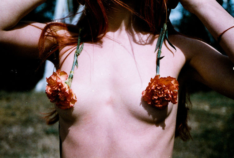 Midsection of sensuous woman with flowers on breasts