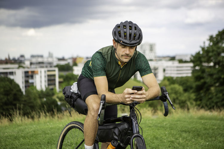 Man using smart phone while sitting on bicycle