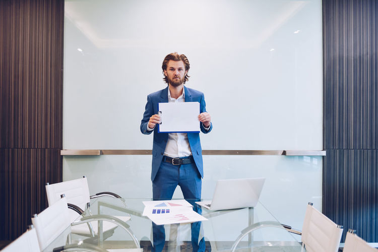 Portrait of businessman standing in conference room