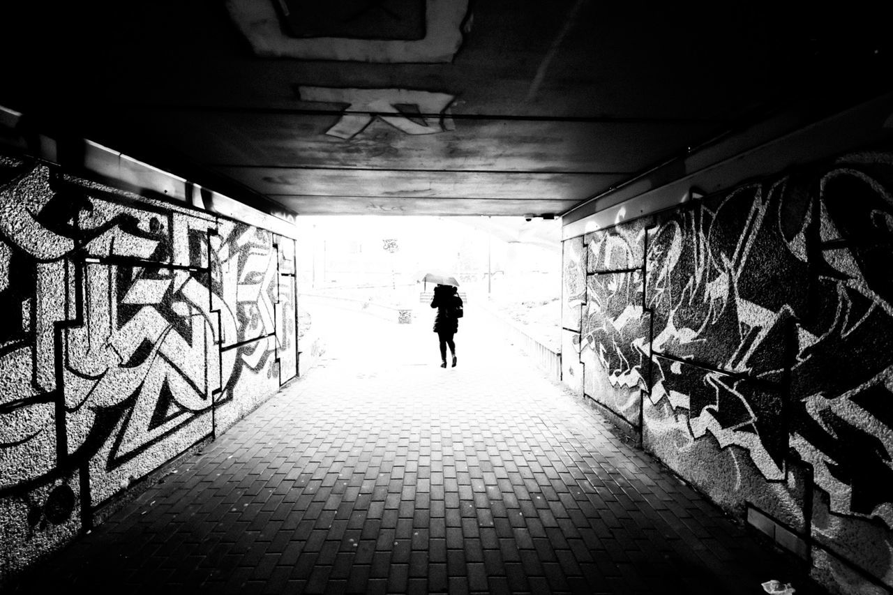 black, architecture, full length, one person, walking, black and white, darkness, white, monochrome, graffiti, built structure, light, rear view, monochrome photography, lifestyles, silhouette, adult, wall - building feature, indoors, the way forward, men, tunnel, city, snapshot, transportation, leisure activity, footpath, day, women, shadow, creativity