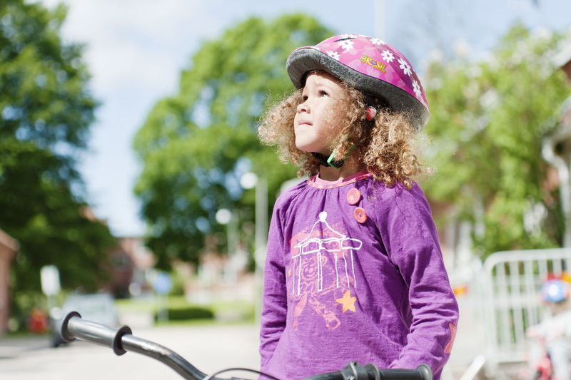 Girl looking away on bicycle in park