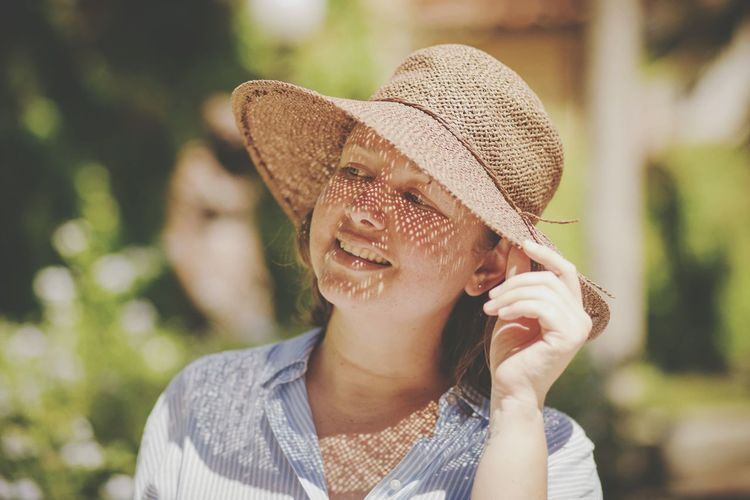 Close-Up Of Mid Adult Woman Wearing Hat While Standing At Park