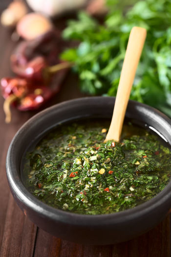 Raw homemade Argentinian green Chimichurri or Chimmichurri salsa or sauce made of parsley, garlic, oregano, hot pepper, olive oil, vinegar, served in rustic bowl, photographed with natural light (Selective Focus, Focus one third into the image) Chimichurri Chimmichurri Garlic Green Homemade Homemade Food Raw South American Food Spicy Argentinian Food Barbecue Condiment Food Food And Drink Fresh Freshness Herb Oregano Parsley Raw Food Ready-to-eat Salsa Sauce Spice Vegetable