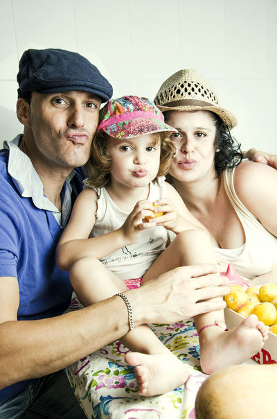 Casual Clothing Enjoyment Family Family Having Fun Family Of Three Family Time Family With Hats Folks Doing Kisses Front View Happiness Happy Family Hats Kissing At Camera Love Portrait Sitting To Pout Togetherness Young Family