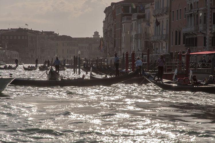People on boats in grand canal against buildings