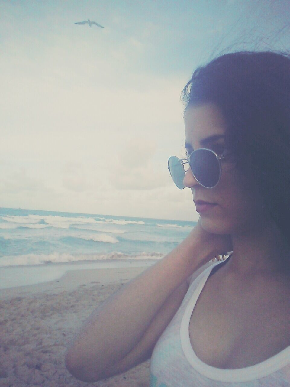 YOUNG WOMAN WEARING SUNGLASSES AT BEACH