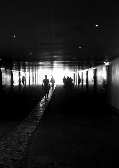 Silhouette people at illuminated underground walkway