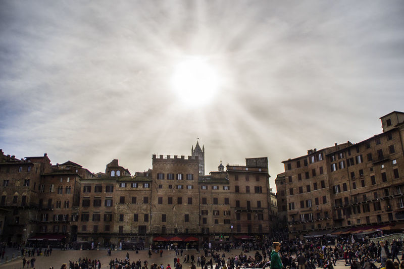 Crowd at piazza del campo against sky on sunny day in city