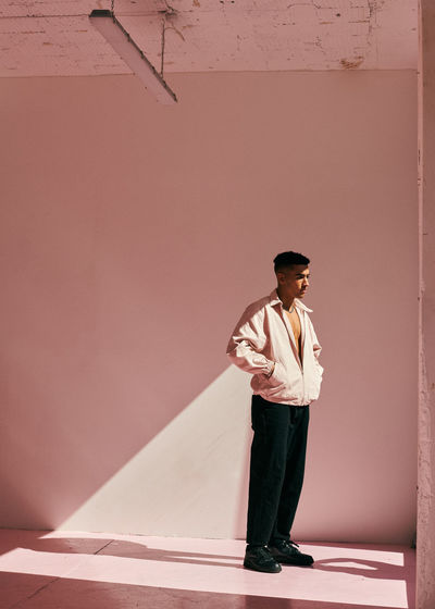 Young man looking away against wall