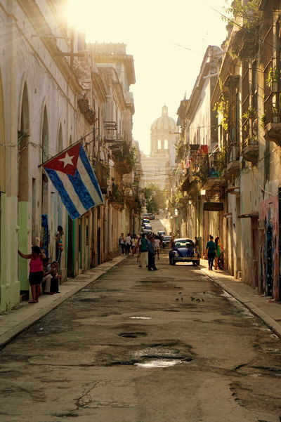 Sunset in streets of Havana, Architecture Building Exterior Built Structure City City Life Cuba Cuban Flag Day Diminishing Perspective Havana Havana, Cuba Land Vehicle Long Men Mode Of Transport Narrow Outdoors Person Sky Street Sunset Sunset Silhouettes The Way Forward Transportation Vanishing Point