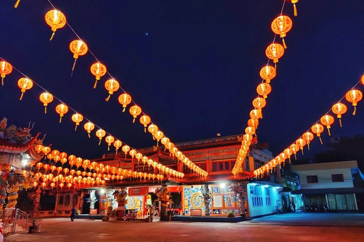 Illuminated lanterns hanging by building against sky at night