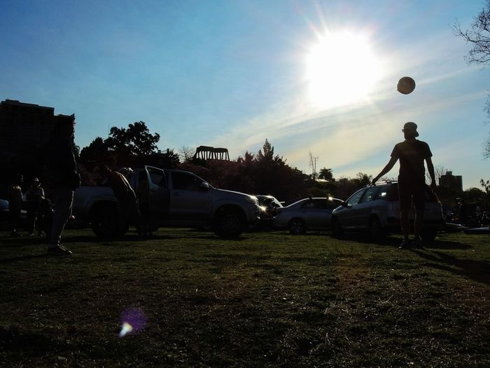 A boy plays football in sunset Argentina Car City City Life Day Futbol Land Vehicle Lens Flare Mode Of Transport Nikon No People Outdoors Parked Parking Parking Lot Silhouette Stationary Street Streetphotography Sun Sunlight Sunset Surface Level Transportation Vehicle