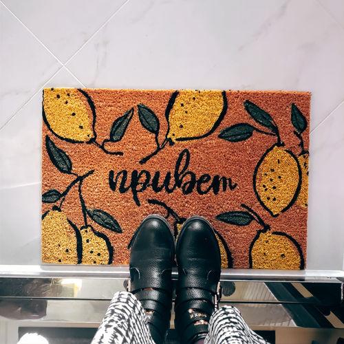 Low section of women standing on doormat