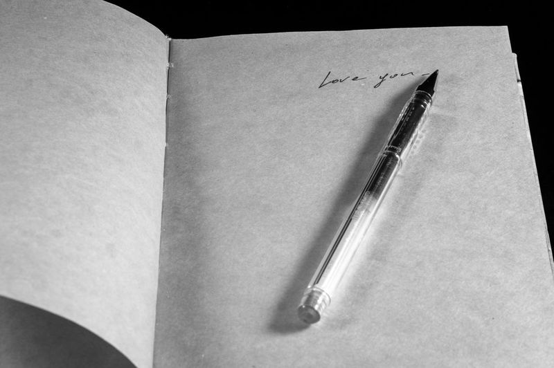 High angle view of pen on open book against black background