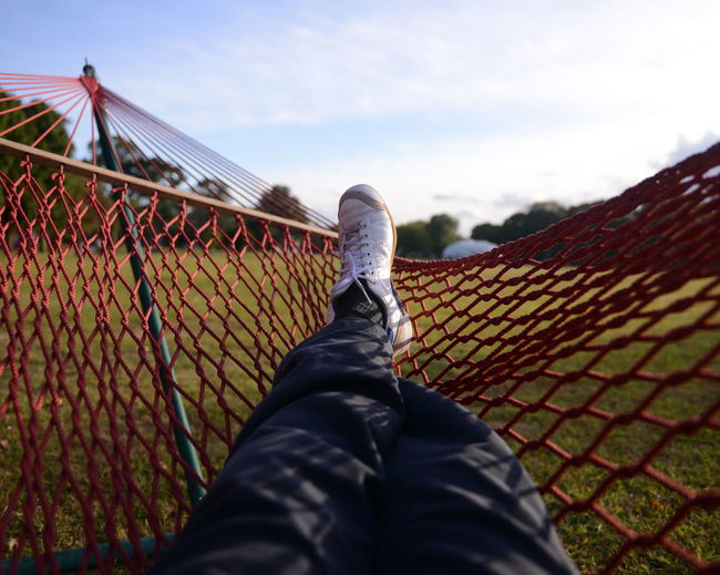Low section of man relaxing on hammock in park against sky