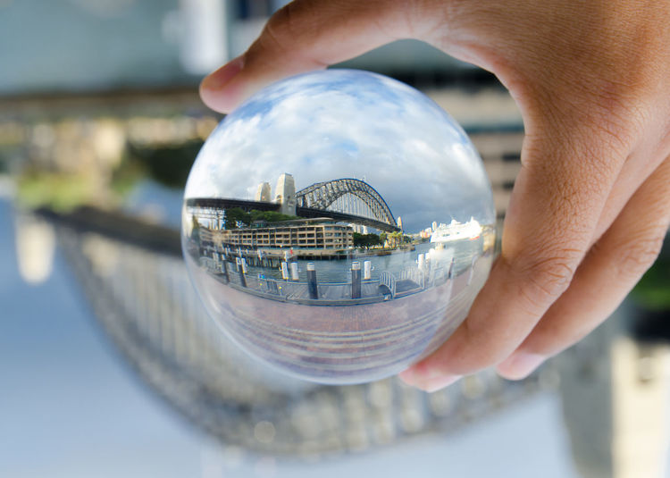 Cropped hand holding crystal ball with reflecting of bridge against cloudy sky