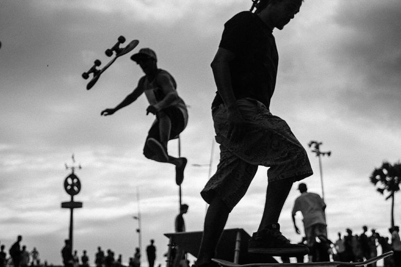 Low Angle View Of Men Skateboarding Against The Sky