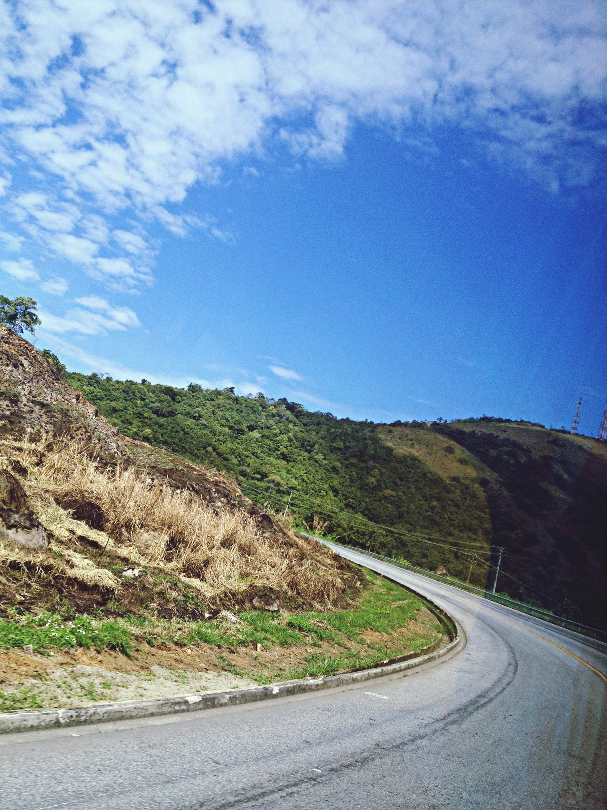 road, the way forward, transportation, sky, country road, road marking, landscape, tranquil scene, tranquility, mountain, diminishing perspective, empty road, scenics, cloud - sky, vanishing point, nature, cloud, empty, beauty in nature, countryside