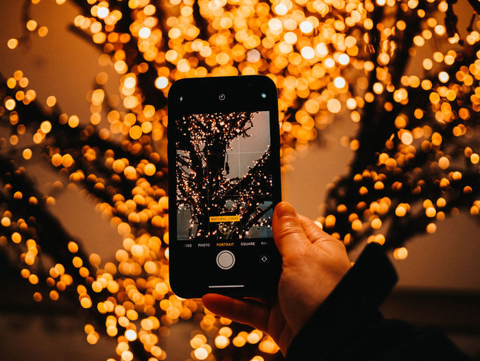 Midsection of person photographing illuminated mobile phone at night