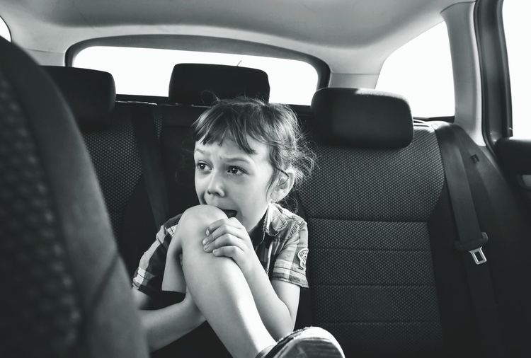 Close-up of crying boy sitting in car