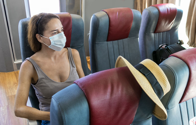 Woman sitting on ferry ship with a surgical mask during covid-19 with empty seats.