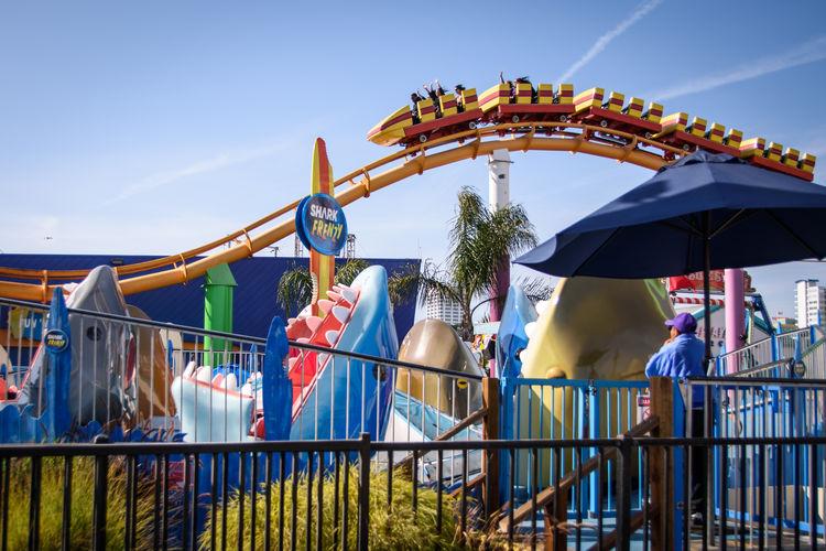 People at amusement park ride against blue sky