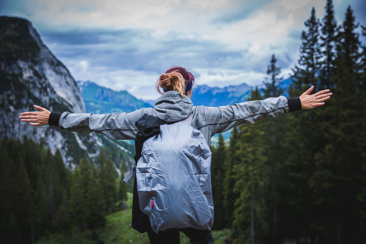 Rear View Of Woman With Arms Outstretched Standing Against Mountain