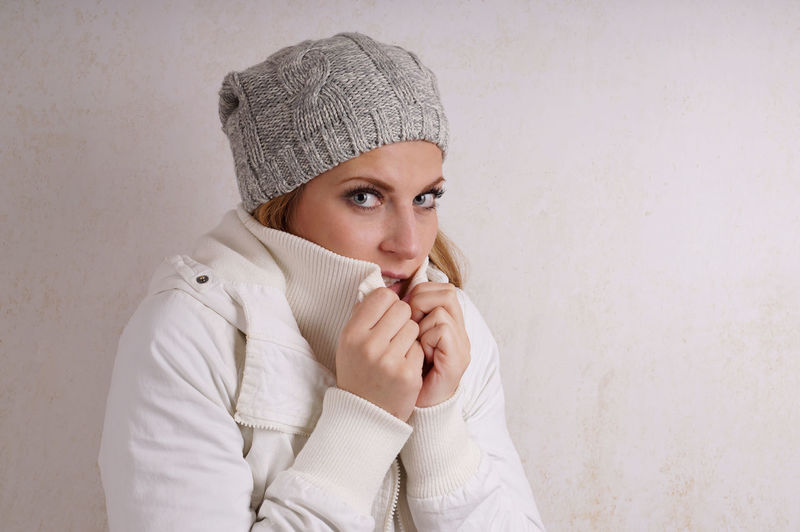 Portrait Of Young Woman Wearing Warm Clothing Against Wall