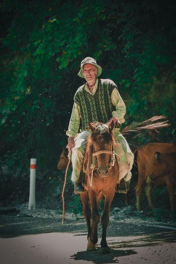 Senior man horseback riding against trees