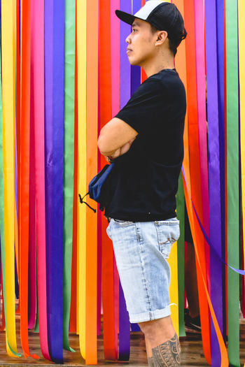 Side view of man wearing cap while standing by colorful ribbons