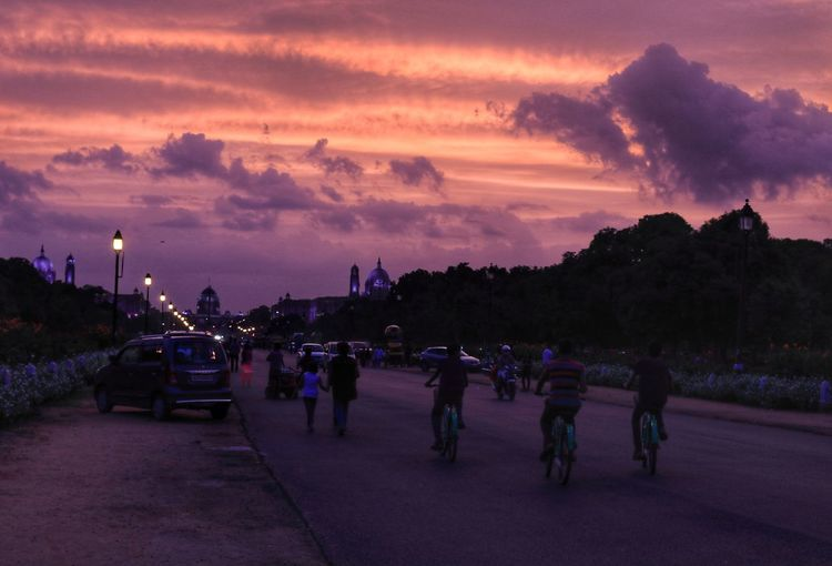 People on street in city against sky at sunset