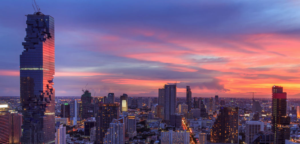 Modern buildings against cloudy sky during sunset