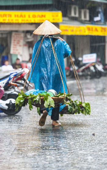 Rear view of person walking on wet street during monsoon