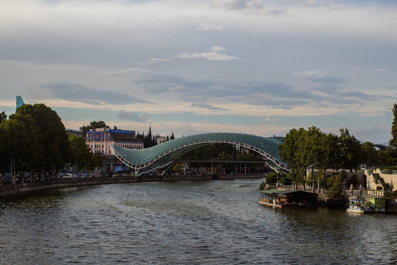 bridge - man made structure, connection, architecture, built structure, river, transportation, tree, water, sky, cloud - sky, bridge, waterfront, no people, day, outdoors, building exterior, nature, city