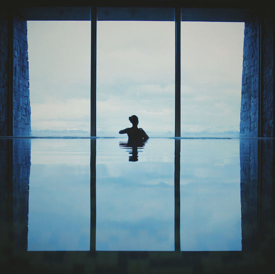 Rear view of silhouette woman swimming in infinity pool