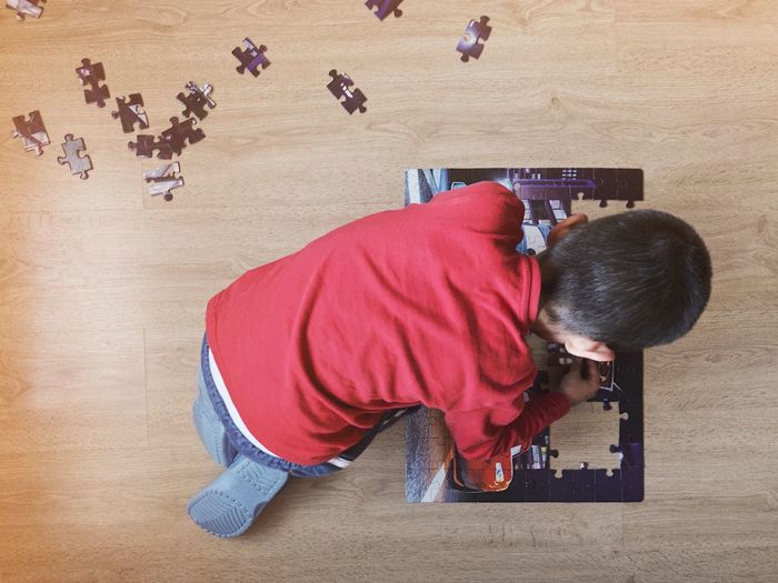 High Angle View Of Boy Solving Puzzle On Hardwood Floor