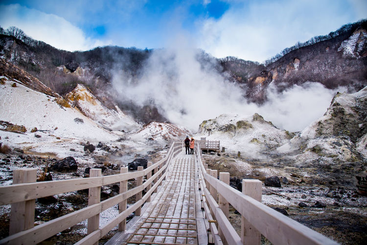 Footbridge on snowcapped mountains against sky
