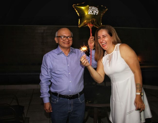 Portrait of man and woman holding illuminated sparkler and balloon wit text at night