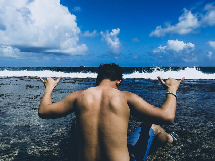 Rear view of shirtless man gesturing while sitting at beach against sky
