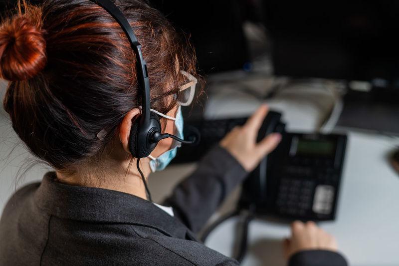 Rear view of woman using landline